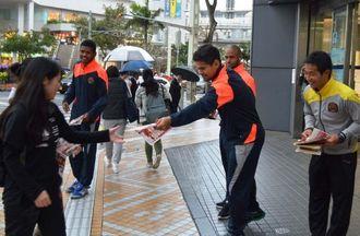 開幕戦のチラシを配りながら、復興支援を呼び掛けるFC琉球のメンバー=10日、那覇市久茂地