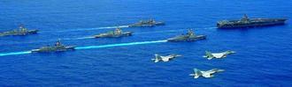 沖縄県東沖を航行する米原子力空母カール・ビンソン(先頭)と海上自衛隊の護衛艦(手前の2隻)など。飛行するのは共同訓練する航空自衛隊の戦闘機(先頭)と空母の艦載機=28日(航空自衛隊提供)