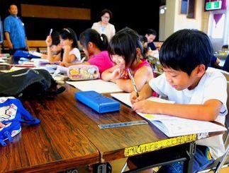 みんなで楽しみながら夏休みの宿題に取り組む子どもたち=24日、宜野湾市愛知区公民館