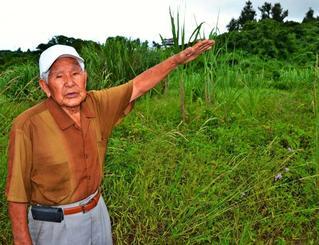 82年前に夜間耕作隊が農作業をしていた場所で当時の状況を説明する比屋根朝栄さん=11日、沖縄市古謝