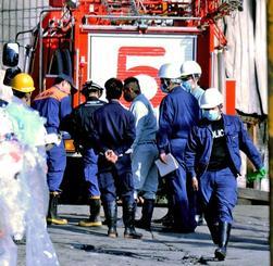 工場関係者立ち会いの下、現場で実況見分する県警の捜査員と糸満市消防本部の隊員=4日午前9時55分ごろ、糸満市大里