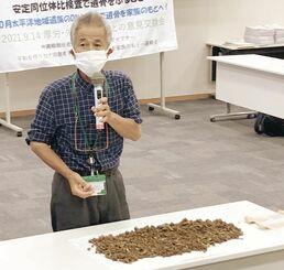 土砂に混じった遺骨について説明する具志堅隆松氏=14日、国会内