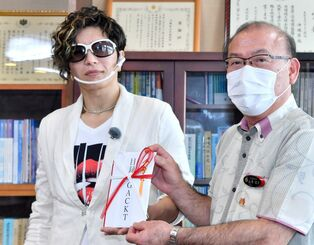 沖縄県土木建築部の上原国定部長(右)に首里城火災復旧支援寄付金目録を手渡し記念撮影するミュージシャン・俳優のGACKTさん=25日、県庁