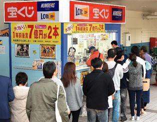 大安吉日に「年末ジャンボ宝くじ」を求め、売り場に行列をつくる人たち=17日午後、サンエー那覇メインプレイスチャンスセンター