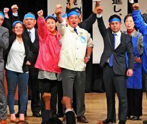 ガンバロー三唱で気勢を上げる佐喜真淳氏(中央)ら=14日、宜野湾市民会館