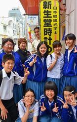 似顔絵看板の下で微笑む西剛志さん(最上段中央)と仲西中の生徒ら=4月30日、浦添市屋富祖の新生堂時計めがね店
