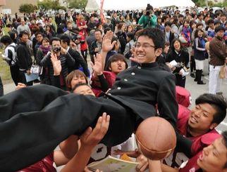 胴上げで合格を祝福される受験生=7日午前、西原町・琉球大学
