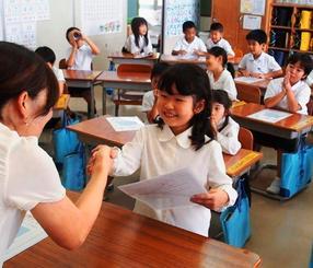 「よいこのあゆみ」を受け取り、笑顔で先生と握手する児童=6日、沖縄市立宮里小学校(鈴木実撮影)