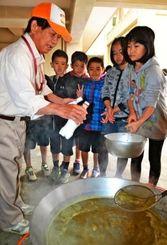 石灰を加え、サトウキビの搾り汁を固める島袋哲行さん(左)と児童=12日、島袋小学校