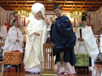指輪を披露する松元孝太さん(右)と華織さん=15日、那覇市の護国神社