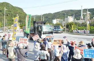 辺野古の埋め立て用土砂を桟橋に運び入れるダンプカーに抗議する市民=27日、名護市安和