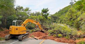 台風8号の大雨に伴う土砂崩れで県道70号をふさいだ土砂の撤去作業を行うショベルカー=25日午前10時半すぎ、国頭村奥(粟国雄一郎撮影)