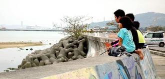 安慶名静枝さんの散歩コースだった泡瀬干潟を望む護岸通り。年始の昼下がり、近所の子どもたちが釣り糸を垂れていた=4日、沖縄市