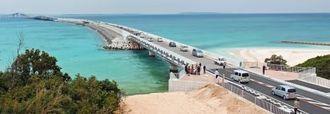 エメラルドグリーンの海に架かった伊良部大橋。開通と同時に多くの車両が走った=31日、伊良部島から望む(アイラス航空、ネクストアース提供、マルチコプターから撮影)