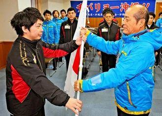 喜納武信団長(右)が新里大旗手に団旗を手渡す