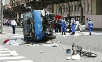 車が暴走し、歩行者が巻き込まれた事故現場を調べる警察官=4月、東京都豊島区