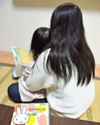 今秋出産予定の第2子の母子手帳のそばで、1歳9カ月の長女に本の読み聞かせをする女性=20日、佐賀県内(提供)