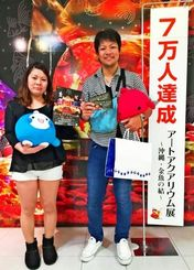 7万人目の入場者となった西江雄太さん、涼子さん夫妻=1日、那覇市・デパートリウボウ