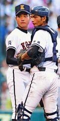 5回表無死一、二塁のピンチで、ベンチのサインを確認する興南エース・比屋根雅也(左)と捕手の佐久本一輝(松田興平撮影)
