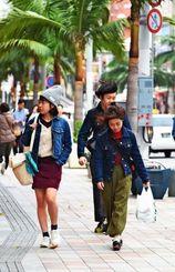 強い風を受けながら国際通りを歩く人々=24日午後、那覇市牧志