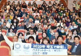 「都市ボランティア」の研修を終え、出席者と記念撮影に納まるナダルさん(前列左端)、岡崎朋美さん(同中央)ら=22日午後、さいたま市
