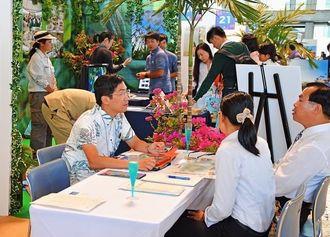国内外のバイヤーに、沖縄のMICE開催の魅力をアピールする県内の出展事業者ら=30日、宜野湾市・沖縄コンベンションセンター