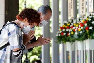 終戦の日を前に、千鳥ケ淵戦没者墓苑で手を合わせるマスク姿の夫婦=14日午後、東京都千代田区