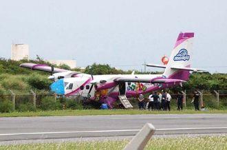 滑走路を逸脱した事故機を調べる警察官ら=29日午前11時半ごろ、粟国空港
