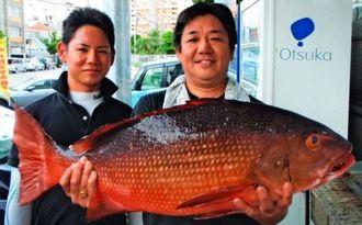 慶良間の磯で83センチ、9・94キロのカースビーを釣った米須剛さん(右)=11日