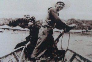 かつて塩屋湾を渡り人や物資を運んでいた渡し船「ティンマ」の様子。学生服姿は宮城村長=1961年ごろ
