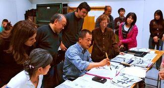 アルゼンチンの県人会館で手本を見せる浜野龍峰さん(中央)=5月9日、ブエノスアイレス(本人提供)