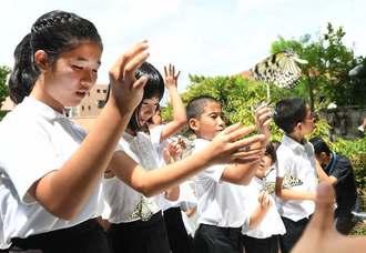 平和を願いオオゴマダラを放つ子どもたち=22日午前、那覇市・小桜の塔