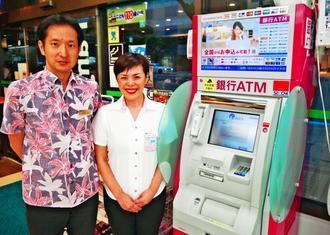しまくとぅばであいさつする「ご当地言葉ATM」と声を担当した仲田直子さん(右)と五月女友彦調査役=日、那覇市内
