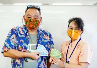 クーポンをPRする(左から)沖縄市観光物産振興協会の山田一誠事務局長、市観光振興課の安慶名豊美課長=5月28日、沖縄市役所