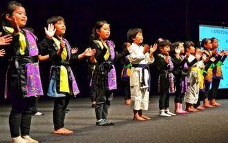 「結んで開いて」をしまくとぅばで歌う子どもたち=1月31日、西原町さわふじ未来ホール