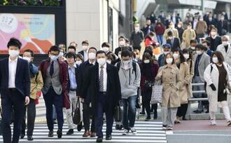 朝の通勤時間帯にマスク姿で歩く人たち=10日、東京・新宿駅付近