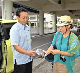 電子チケットによる乗車のデモンストレーションで、運転手にスマホを提示する女性=26日、石垣市美崎町の石垣港離島ターミナル