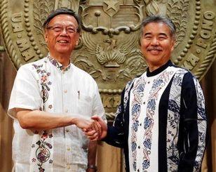 翁長雄志知事(左)と会談を終え、握手するハワイ州のデービッド・イゲ知事=29日午前、ホノルル市のハワイ州庁