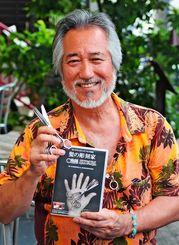 「髪の彫刻家」を発売した美容師のカズレ・ミヤラ(本名・宮良長和)さん=那覇市・桜坂劇場