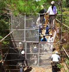 N1裏に新たにフェンスを設置する作業員。手前には有刺鉄線が張り巡らされた=27日午後1時半、国頭・東村境