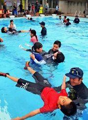 あおむけに浮く姿勢の取り方を学ぶ児童ら=14日、東村・有銘小中学校