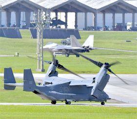 滑走路を走る米空軍CV22オスプレイ。中央に最新鋭ステルス戦闘機F22、奥にF15戦闘機=2018年6月5日、米軍嘉手納基地