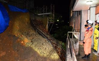 建設現場で土砂崩れが起こり、擁壁がなぎ倒された=16日午後10時ごろ、北谷町桑江(勝浦大輔撮影)