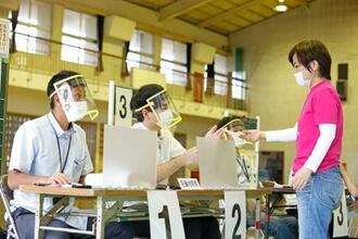 沖縄県議選の投票所で、フェースシールドを着け受け付けをする選管の係員=7日午前、那覇市