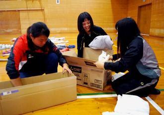 集まった野球道具を箱に詰める八重山商工高の生徒たち(提供)