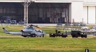 不時着から一夜明け、渡名喜村を離陸後、嘉手納基地に立ち寄ったAH1Z攻撃ヘリからロケット訓練団を降ろす米兵ら=24日、米軍嘉手納基地(読者提供)