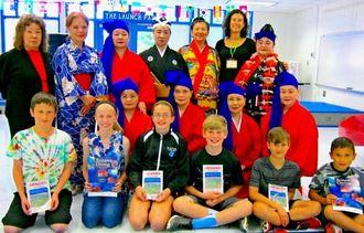 学校訪問をしたアトランタ沖縄県人会員とリナ・マーテンさん(後列右から2人目)、5年生たち(前列)=ピープルズ小学校