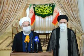 19日、イラン・テヘランで記者会見するロウハニ大統領(左)とライシ次期大統領(イラン大統領府提供、AP=共同)