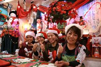 「メリークリスマス!」と笑顔を見せる島袋洋子さん(右端)と従業員=22日、うるま市石川の「夢見る天使」