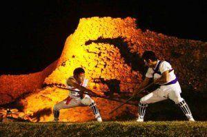 今帰仁村青年祭りで、ライトアップされた城壁を前に棒術を披露する今泊青年会=2012年1月、今帰仁城跡